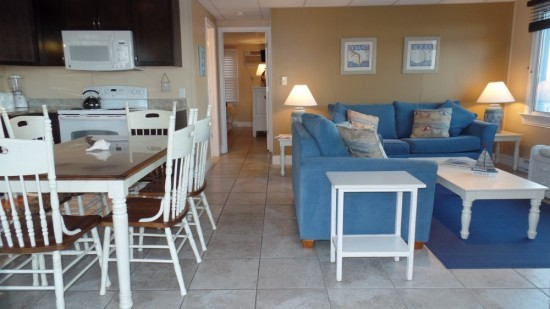 two bedroom condo with kitchen, living area and bathroom. Blue and yellow accents and brown and white dining room table