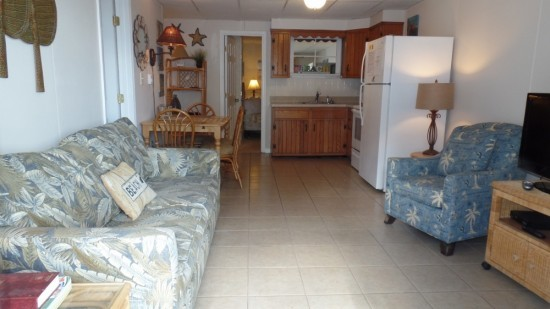 ocean city condo for rent with large living room space with refrigerator large screen televisiob, and seating options