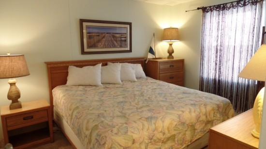 Master bedroom in rental with king sized bed, dresser, nightstand, and another tall dresser for storage.