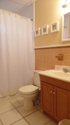 Small bathroom with tile flooring, a bathtub, sink, light wood cabinetry, and yellow walls.