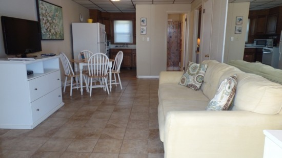 Tile floors, TV stand, light beige couch and entry way to kitchen are all available in the living space.