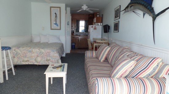 studio in ocean city with couch, bed and small kitchen to cook. Light blue walls and beach accents, small dining room table