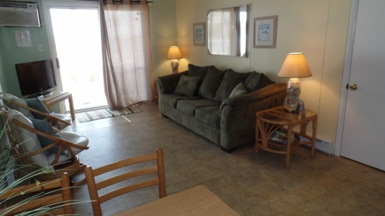 large family room in rental at ocean city with large couch, chairs for seating and a television. Also included a sliding door for balcony access.