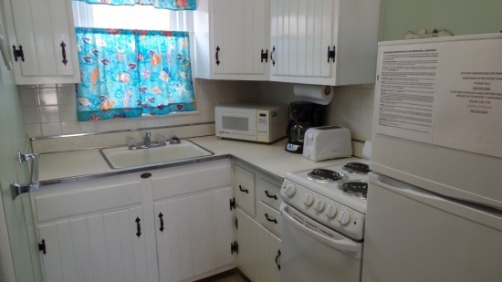 Kitchen with white cabinetry and white appliances. Included stove, oven, fridge, large sink, toaster and coffee pot.