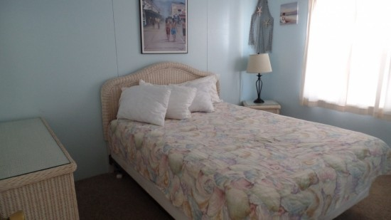 small bedroom in rental with full sized bed, light blue walls, night stand and dresser for storing clothes