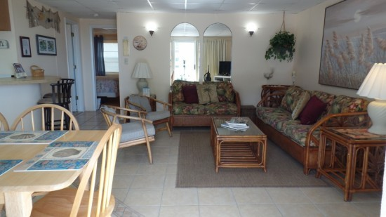 ocean city md rental with a large living room, a couch and love seat, two extra chairs with a leafy vibe to it
