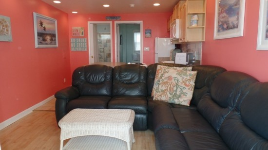 large living room in condo with black pleather wrap around couch, a wicker coffee table and plenty of walking space