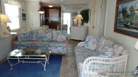 A two couch living room in condo. Includes pink and blue floral couches, glass coffee table, blue area rug with