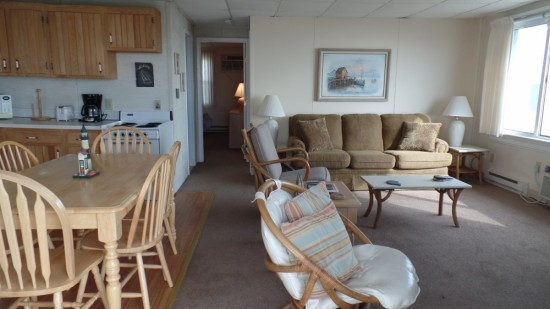 Ocean City, MD condo with large family room with a couch, rocking chairs along with a kitchen table
