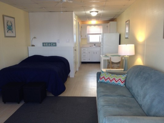 small studio in ocean city with a bed and couch, and light yellow walls