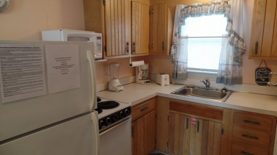 Kitchen with light wooden paneled cabinets and counter space. Includes all appliances like a blender, coffee pot and toaster.