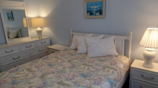 Light blue bedroom in ocean city condo with a queen sized bed with seashell bedding and white accents. Plenty of drawer space and plenty of lighting