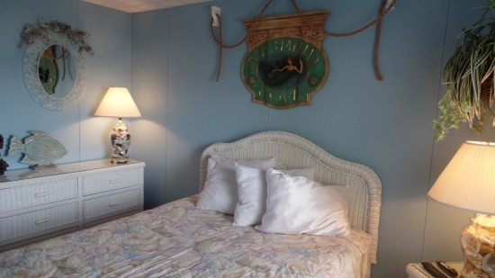 Under the sea bedroom with full bed, blue walls, and ocean decor. Includes a white dresser and two lamps